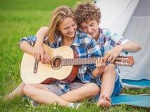Adolescent et fille près de la tente jouant une guitare dehors Image stock