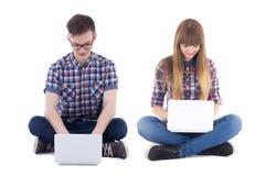 Adolescent et fille s'asseyant avec des ordinateurs d'isolement sur le blanc Photographie stock