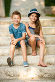 Adolescent et fille s'asseyant sur des escaliers en parc Images libres de droits