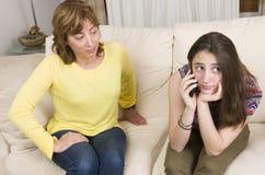Adolescent et sa mère ayez un argument au sujet de son téléphone à la maison photographie stock