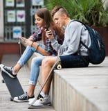 Adolescent et son amie avec des smartphones Image stock