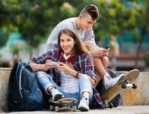 Adolescent et son amie avec des smartphones Images stock