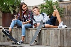 Adolescent et son amie avec des smartphones Photographie stock libre de droits