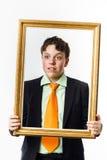 Adolescent expressif posant avec le cadre de tableau images stock