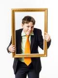 Adolescent expressif posant avec le cadre de tableau photo stock