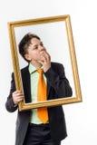 Adolescent expressif posant avec le cadre de tableau photos libres de droits