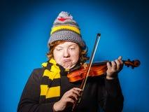 Adolescent expressif roux jouant le violon, concept drôle photos stock