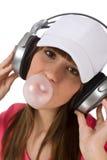 Adolescent féminin avec le bubble-gum et les écouteurs Photos libres de droits