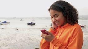 Adolescent féminin Biracial écoutant la musique sur les écouteurs sans fil utilisant son téléphone portable intelligent clips vidéos