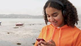 Adolescent féminin Biracial écoutant la musique sur les écouteurs sans fil utilisant son téléphone portable intelligent banque de vidéos