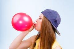 Adolescent féminin gonflant le ballon rouge Image libre de droits