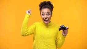 Adolescent féminin montrant le geste de succès appréciant le jeu vidéo, passe-temps rond de gain photo libre de droits
