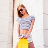 Adolescent féminin se tenant avec la planche à roulettes Image libre de droits