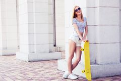 Adolescent féminin sexy dans des lunettes de soleil tenant la planche à roulettes Photos libres de droits