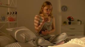 Adolescent féminin triste mâchant la douleur abdominale se sentante de beignet, santé de manger avec excès d'effort clips vidéos