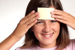 Adolescent face with a blank yellow sticky note. Pretty smiling adolescent face with a blank yellow sticky note stuck to her forehead royalty free stock image