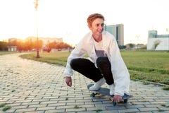 Adolescent faisant de la planche à roulettes en parc un jour de congé par temps ensoleillé Photo stock