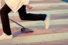 Adolescent faisant de la planche à roulettes en parc un jour de congé par temps ensoleillé Image stock