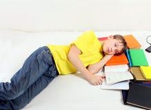 Adolescent fatigué avec livres Photo stock