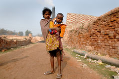 Adolescent girl in brick-field. March 08,2011 Khariberia,West Bengal,India,Asia -A adolescent labour holding her brother royalty free stock photo
