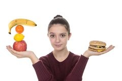 Young girl with fruit and a hamburger. Adolescent girl choosing between fruit and a hamburger on a white background Royalty Free Stock Photos