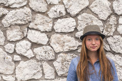 Adolescent girl in a hat and denim jacket against a white stone walls. Walk. Stock Photo