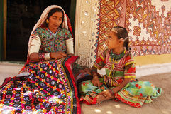 Adolescent Girl in rural Gujarat-India. February 19, 2012-Gujarat,Ran of kutch,India,Asia-A Lambada tribal woman doing art work beside her adolescent daughter in Stock Photo