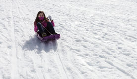 Adolescent girl sledding. Adolescent girl on sled in snow stock photos