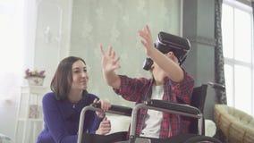 Adolescent handicapé dans un fauteuil roulant et sa maman à la maison, utilisant le plan rapproché de technologie de vr clips vidéos