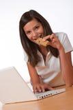 Adolescent heureux avec l'ordinateur portatif mangeant le bar de protéine photos libres de droits