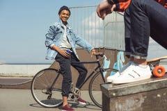Adolescent heureux avec la bicyclette en parc de planche à roulettes Photo stock