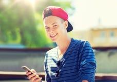 Adolescent heureux avec le smartphone dehors Photos libres de droits