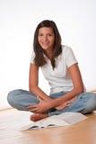 Adolescent heureux s'asseyant avec le livre Photographie stock libre de droits