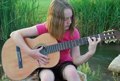 Adolescent jouant la guitare Image stock