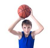 Adolescent joyeux tenant une boule pour le basket-ball au-dessus de sa tête Est Image stock