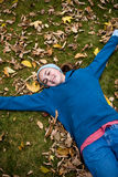 Adolescent laying on ground in autumn Royalty Free Stock Photo