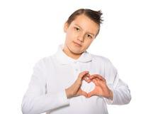Adolescent le garçon montrant la forme de coeur avec des mains Photographie stock libre de droits