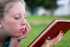 Adolescent looking. An adolescent girl reads a school book in a green field Stock Photography
