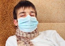 Adolescent malade dans le masque de grippe image libre de droits