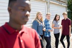 Adolescent malheureux bavardé environ par des pairs photographie stock libre de droits