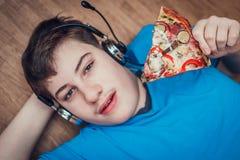 Adolescent mangeant de la pizza photographie stock libre de droits