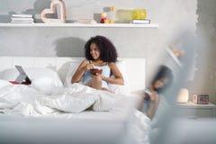 Adolescent mangeant la comédie de observation de petit déjeuner dans le lit Photos stock