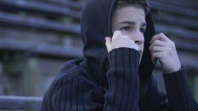 Adolescent masculin seul s'asseyant sur le banc, problèmes d'adolescence, auto-protestation intérieure banque de vidéos