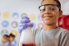 Adolescent optimiste souriant tout en entreprenant l'expérience Image libre de droits