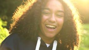 Adolescent ou jeune femme heureux de fille d'Afro-américain de métis bulles riant, de sourire et de soufflement au coucher du sol banque de vidéos