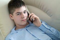 Adolescent parlant au t?l?phone portable se trouvant sur le sofa photographie stock libre de droits