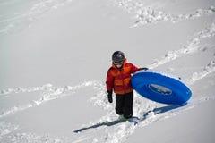 Adolescent portant le tube sledding gonflable vers le haut de la colline neigeuse dans les montagnes Photos libres de droits