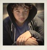 Adolescent préoccupé triste d'école posant la séance extérieure sur la rue vous regardant - fermez-vous du visage avec des couleu photographie stock