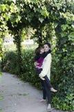 Adolescent prenant sa petite soeur dans le jardin d'une maison Photos stock