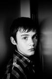 Adolescent sérieux se cachant derrière la porte dans la maison Image stock